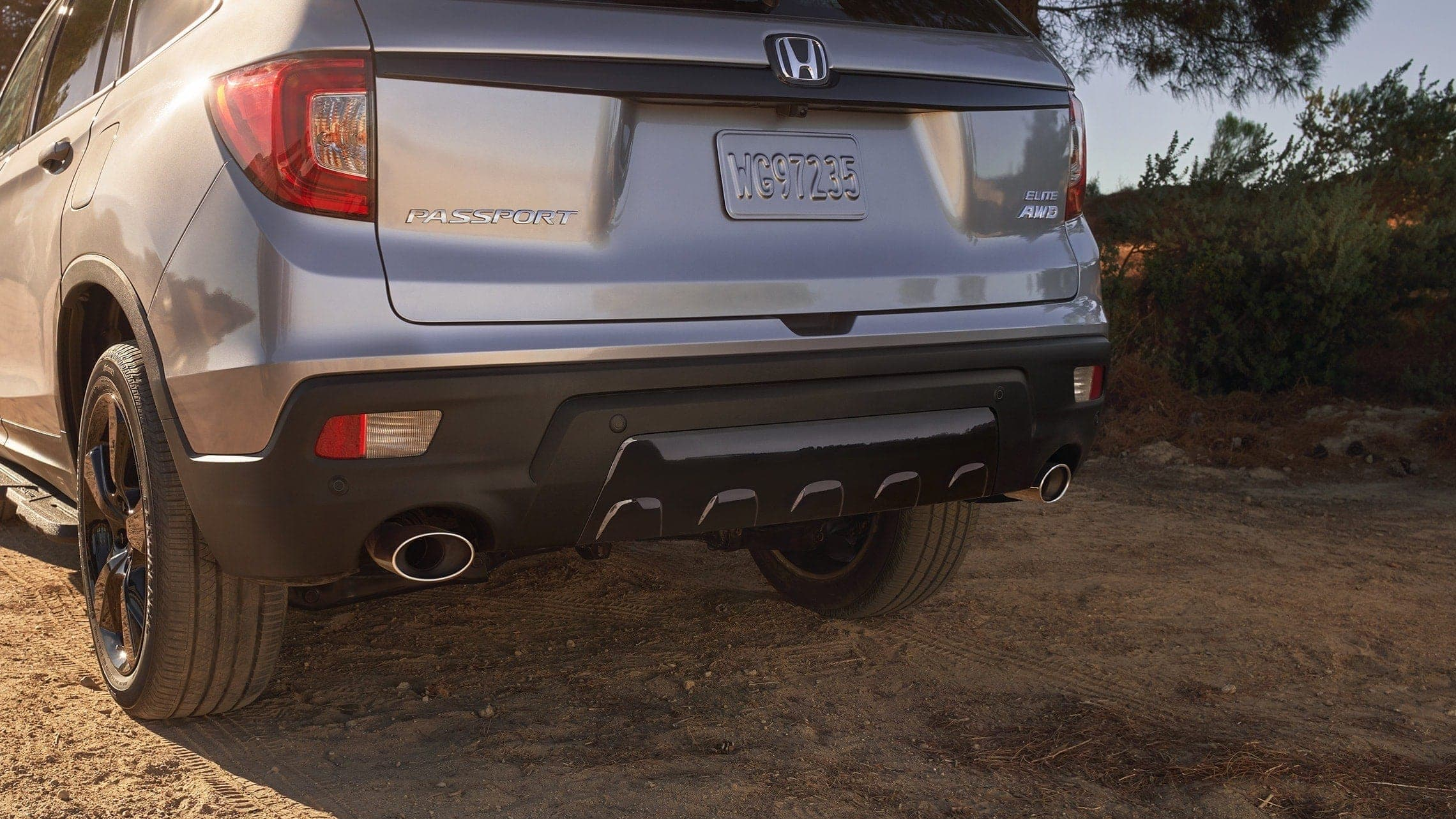 Dual exhaust finishers with parking sensors on the 2019 Honda Passport Elite in Lunar Silver Metallic.